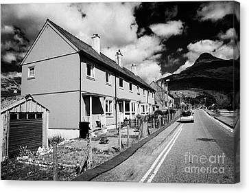 Red Painted Wooden Clad Houses On The Main Street In Glencoe Highlands Scotland Uk With The Pap Of G Canvas Print by Joe Fox