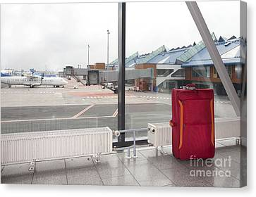 Rolling Luggage In An Airport Concourse Canvas Print by Jaak Nilson
