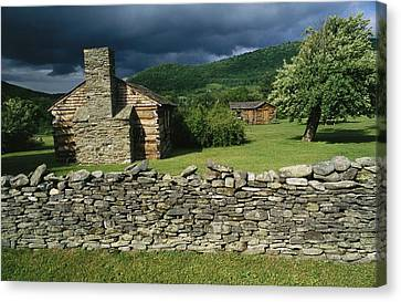 Storm Clouds Form Above Log Buildings Canvas Print by Raymond Gehman
