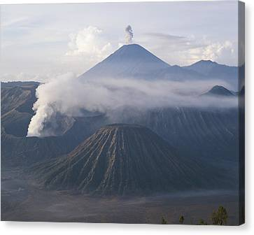 The Peak Of Semaru Rises Above Mount Canvas Print by Carsten Peter