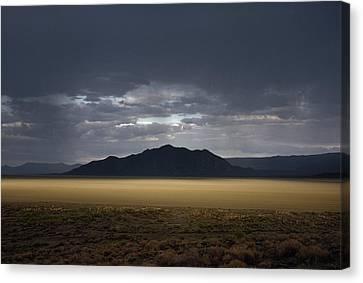 The Setting Sun Permeates Rain Clouds Canvas Print by James P. Blair