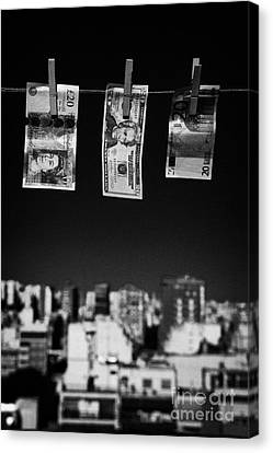 Twenty Pounds Dollars Euro Banknotes Hanging On A Washing Line With Blue Sky Over City Skyline Canvas Print by Joe Fox