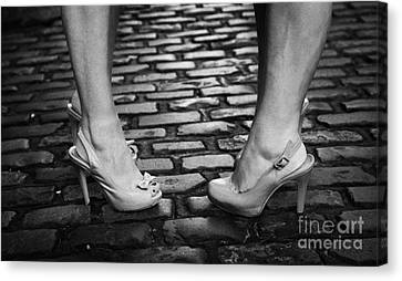 Two Young Women Wearing High Heeled Shoes And Fake Tan On Cobblestones On A Night Out Canvas Print by Joe Fox