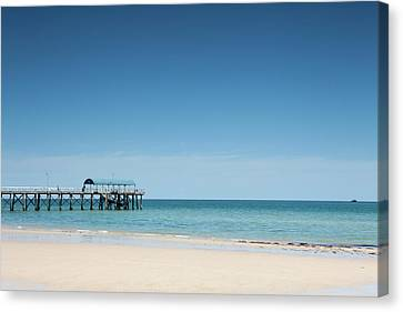View Of A Pier From A Sandy Beach Canvas Print by Caspar Benson