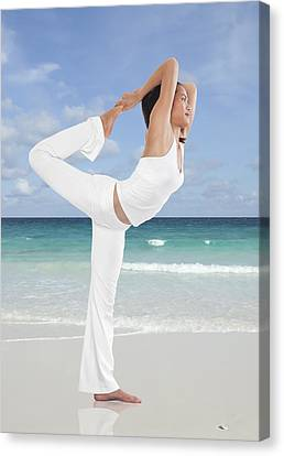 Woman Doing Yoga On The Beach Canvas Print by Setsiri Silapasuwanchai
