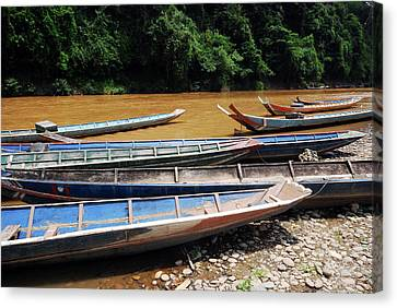 Wooden Boat On River In Laos Canvas Print by Thepurpledoor