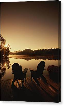 A Pair Of Adirondack Chairs On A Dock Canvas Print by Michael Melford