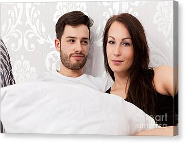 Young Couple Snuggling In Bed Canvas Print by Wolfgang Steiner