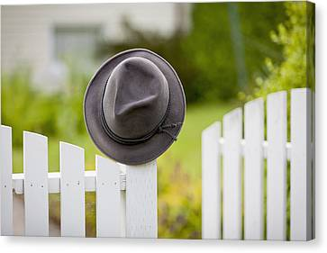 A Hat Hanging On The Post Of A White Canvas Print by Lorna Rande