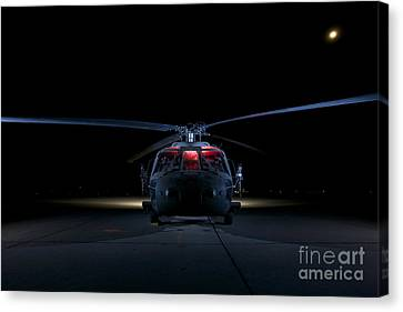 A Uh-60 Black Hawk Helicopter Lit Canvas Print by Terry Moore