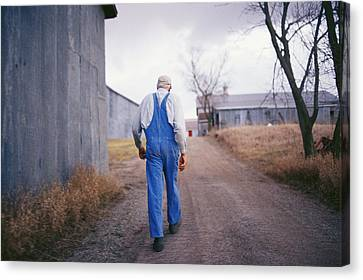 An Elderly Farmer In Overalls Walks Canvas Print by Joel Sartore