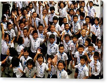 Bangkok School Children Jumping And Smiling At The Camera Canvas Print by Sami Sarkis