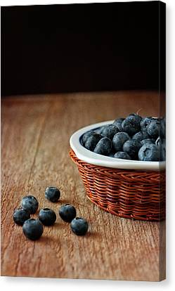 Blueberries In Wicker Basket Canvas Print by © Brigitte Smith
