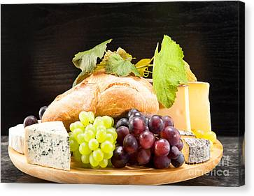 Cheese Plate With Red And Green Wine Grapes Canvas Print by Wolfgang Steiner