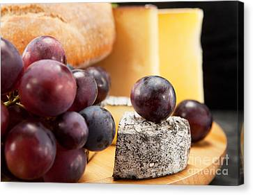 Cheese Plate With Red Wine Grapes And White Bread Canvas Print by Wolfgang Steiner