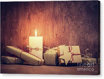 Chistmas Presents, Gifts With A Candle Glowing On Wooden Wall Background. Canvas Print by Michal Bednarek