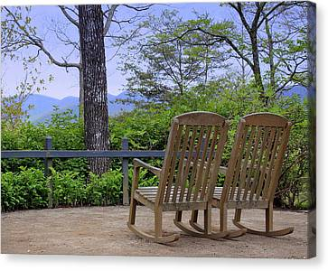A Conversation Between Trees And Two Wooden Rocking Chairs Canvas Print by Katharine Hanna