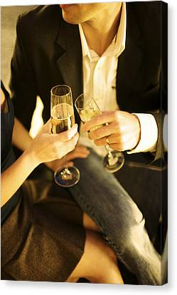 Couple Sitting, Clinking Champagne Canvas Print by Gillham Studios