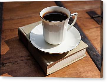 Cup Of Coffee Upon A Closed Book On Wooden Table Canvas Print by Bradley Hebdon