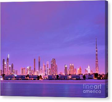 Dubai City Skyline From Emirates Towers To Burj Kalifa Aka Burj Dubai From Jumeirah Beach At Night Canvas Print by Chris Smith