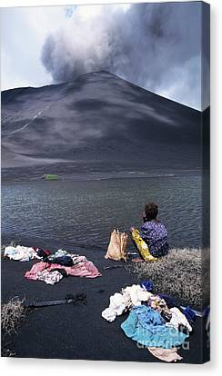 Girl Washing Clothes In A Lake With The Mount Yasur Volcano Emitting Smoke In The Background Canvas Print by Sami Sarkis
