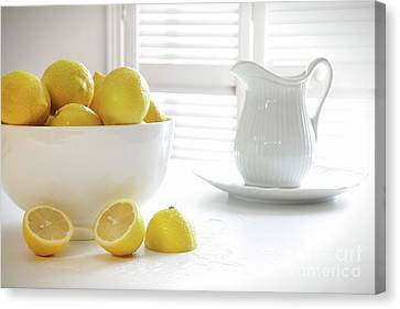 Lemons In Large Bowl On Table Canvas Print by Sandra Cunningham