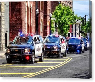 Line Of Police Cars Canvas Print by Susan Savad