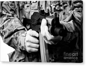 Man In Combat Fatigues Holding Aks-47u Close Quarter Combat Kalasknikov Rifle Focus On Safety Select Canvas Print by Joe Fox