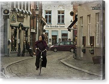 Nun On A Bicycle In Bruges Canvas Print by Joan Carroll