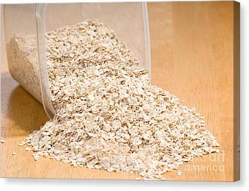 Oat Flakes Spilled Out Of Plastic Container  Canvas Print by Arletta Cwalina