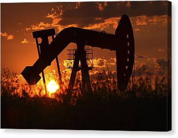 Oil Rig Pump Jack Silhouetted By Setting Sun Canvas Print by Mark Duffy