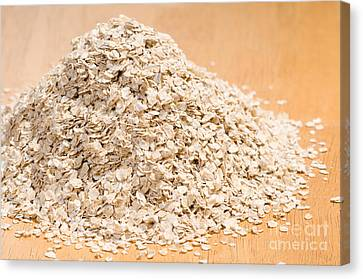 Pile Of Dried Rolled Oat Flakes Spilled  Canvas Print by Arletta Cwalina