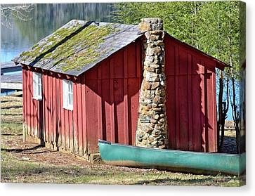 Red Shed And Canoe Canvas Print by Susan Leggett