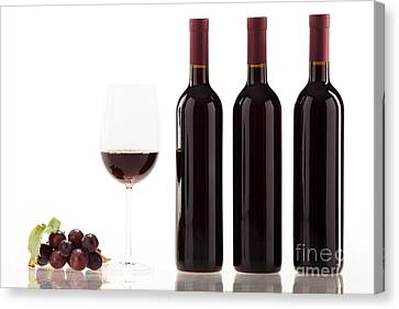 Red Wine In Glass With Fruit Leaves And Wine Bottle Canvas Print by Wolfgang Steiner