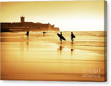 Surfers Silhouettes Canvas Print by Carlos Caetano
