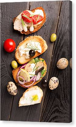 Tasty Tapas On A Wooden Black Table  Canvas Print by Vadim Goodwill