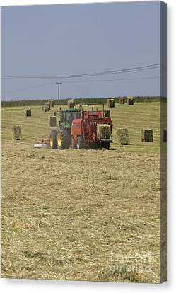 Tractor Bailing Hay In A Field At Harvest Time Pt Canvas Print by Andy Smy