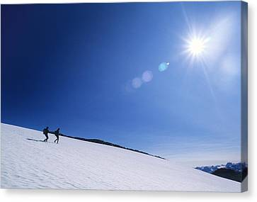 Two Hikers Explore A Snowfield Canvas Print by Bill Hatcher