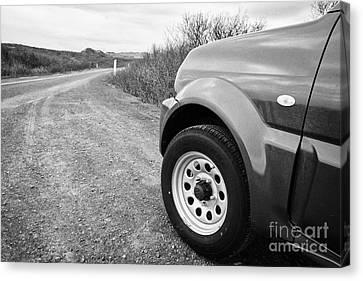 Wheel Of Small 4x4 Vehicle Driving On Gravel Road Onto Main Road Reykjavik Iceland Canvas Print by Joe Fox