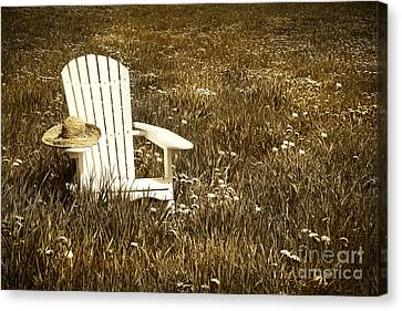 White Chair With Straw Hat In A Field Canvas Print by Sandra Cunningham