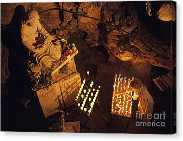 Woman Burning Candle At Troglodyte Sainte-marie Madeleine Holy Cave Canvas Print by Sami Sarkis