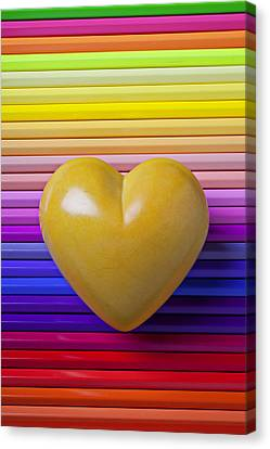 Yellow Heart On Row Of Colored Pencils Canvas Print by Garry Gay