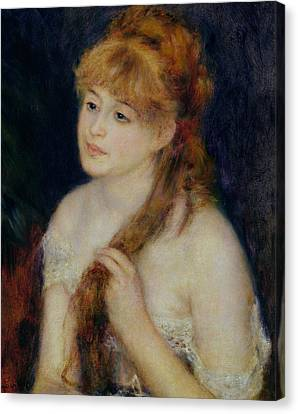 Young Woman Braiding Her Hair Canvas Print by Pierre Auguste Renoir