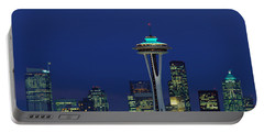 Buildings In A City Lit Up At Night Portable Battery Charger by Panoramic Images