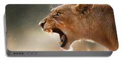 Lioness Displaying Dangerous Teeth In A Rainstorm Portable Battery Charger by Johan Swanepoel