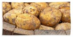 Freshly Harvested Potatoes In A Wooden Bucket Beach Towel by Tom Gowanlock