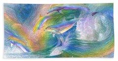 Rainbow Dolphins Beach Towel by Carol Cavalaris