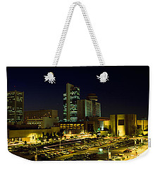 Buildings In A City Lit Up At Night Weekender Tote Bag by Panoramic Images