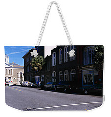 Buildings On Both Sides Of A Road Weekender Tote Bag by Panoramic Images