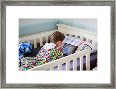 Boy In Bed Using A Digital Tablet Framed Print by Samuel Ashfield